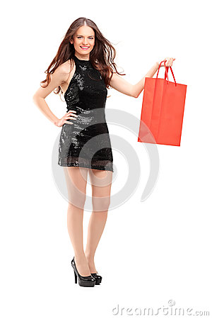 Full length portrait of an attractive woman holding a shopping bag
