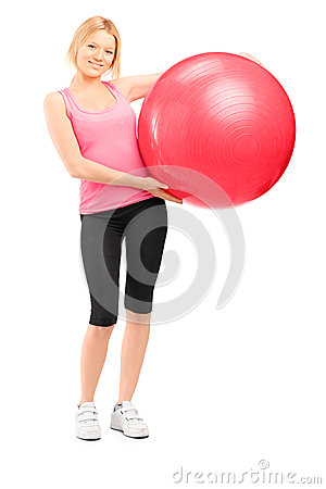 Full length portrait of a blond female athlete holding a pilates