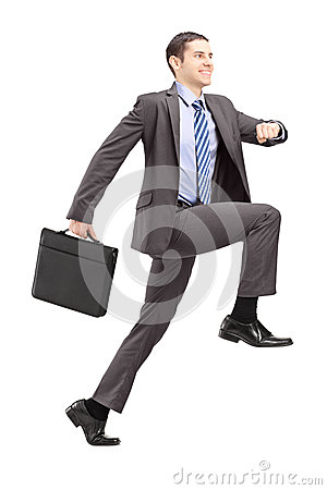 Full length portrait of a businessman doing a huge step towards