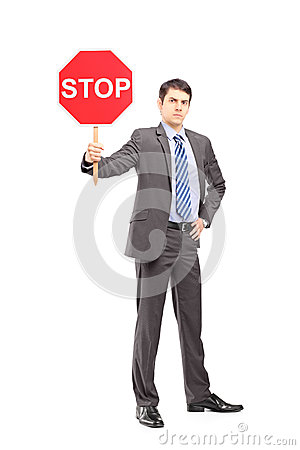 Full length portrait of a businessman holding a stop sign