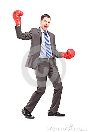 Full length portrait of a businessman wearing red boxing gloves
