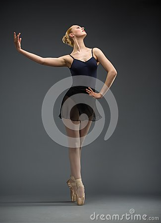 Full-length portrait of dancing ballerina with hand on hips