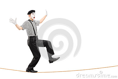 Full length portrait of an excited male mime artist walking on a