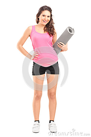 Full length portrait of a female athlete holding a mat