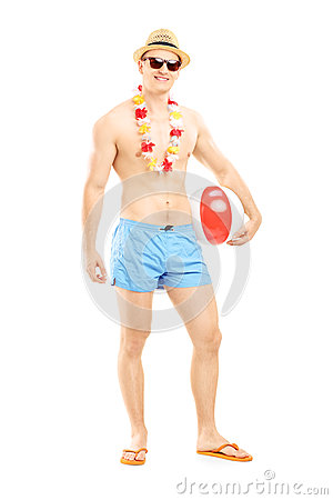 Full length portrait of a fit man in swimming shorts, holding a