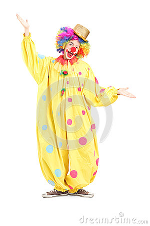 Full length portrait of  a funny circus clown gesturing with han