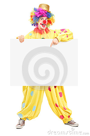 Full length portrait of a happy male clown pointing on a panel