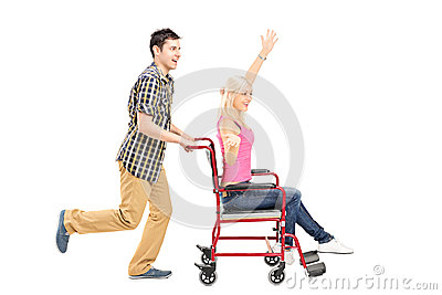 Full length portrait of a happy male pushing a female in wheelch