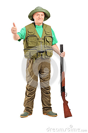 Full length portrait of a hunter holding a rifle and giving a th