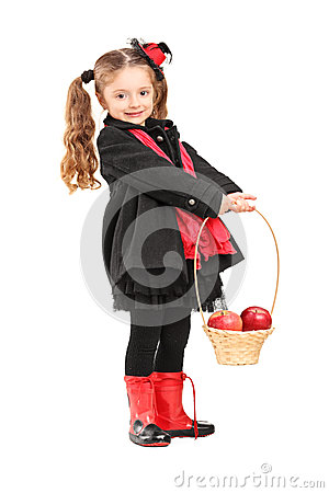 Full length portrait of a little girl holding a basket with appl