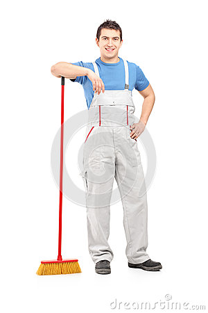 Full length portrait of a male cleaner holding a broom