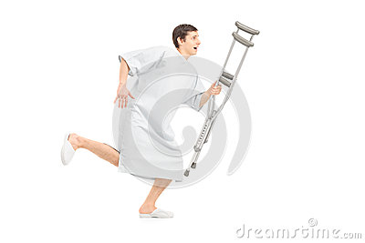 Full length portrait of a male patient running and holding a cru