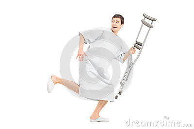 Full length portrait of a male scared patient running and holdin