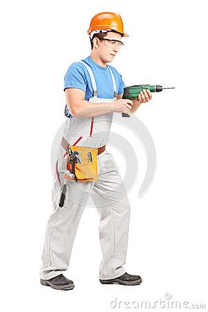 Full length portrait of a manual worker with helmet using a dril