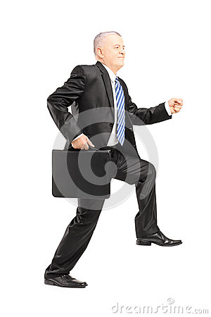Full length portrait of a mature businessman doing a huge step