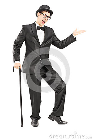 Full length portrait of a performer in black suit gesturing with