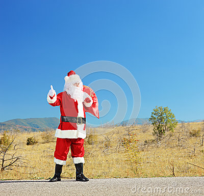 Full length portrait of a santa claus with bag on an open road h
