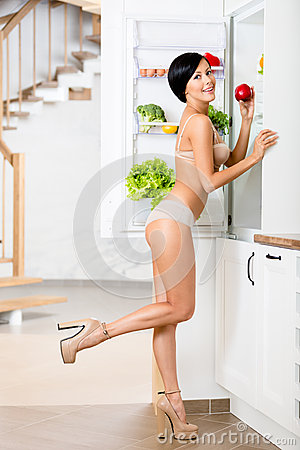 Full-length portrait of woman near the opened refrigerator