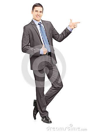 Full length portrait of a young businessman leaning against wall