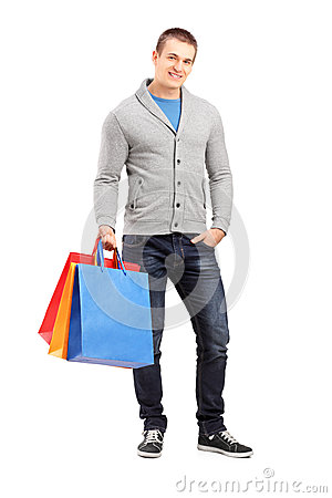 Full length portrait of a young casual man holding shopping bags