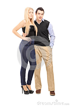 Full length portrait of a young couple standing together and loo