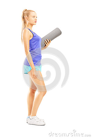 Full length portrait of a young female athlete holding an exerci