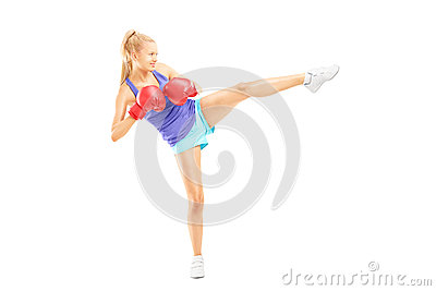 Full length portrait of a young female with boxing gloves hittin