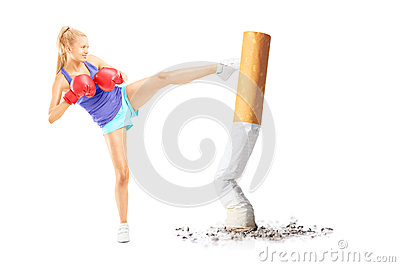 Full length portrait of a young female with boxing gloves kickin