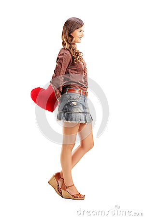 Full length portrait of a young female holding a red heart behin