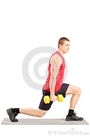 Full length portrait of a young man exercising with weights