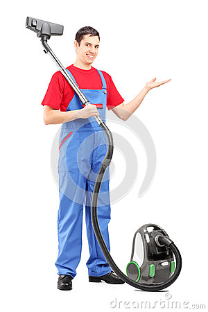 Full length portrait of a young man with a vacuum cleaner