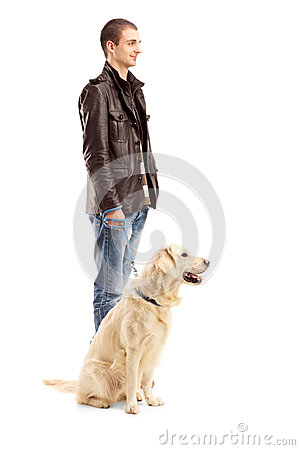 Full length portrait of a young man standing with a retriever dog