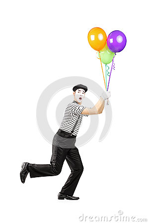 Full length portrait of a young mime artist holding balloons