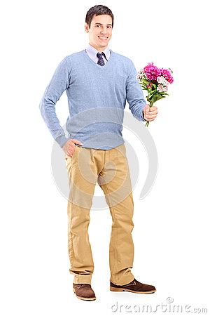 Full length portrait of a young romantic man holding a bouquet