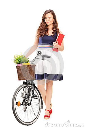 Full length portrait of a young woman with a bicycle