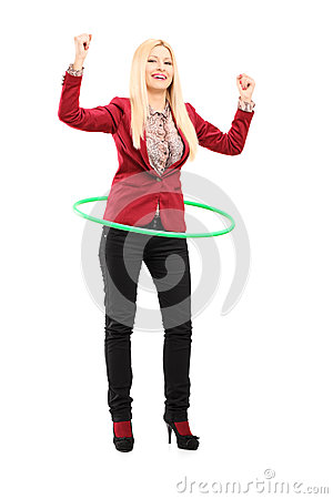 Full length portrait of a young woman dancing with a hula hoop