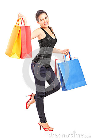 Full length portrait of a young woman holding shopping bags