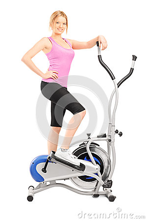 Full length portrait of a young woman posing on a cross trainer