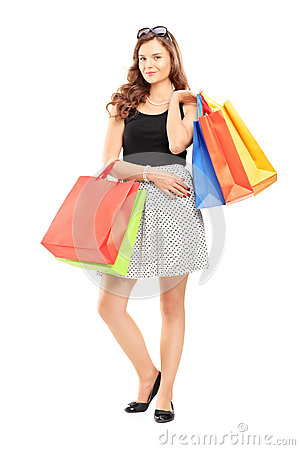 Full length portrait of a young woman posing with shopping bags