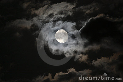 Full moon in eerie white clouds against a black ni