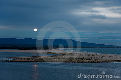 Full moon rising over lake & sea landscape at dusk