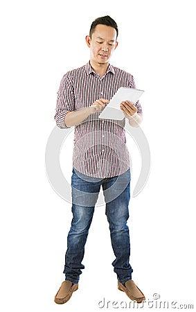 Fullbody asiatischer Mann, der Tablette verwendet
