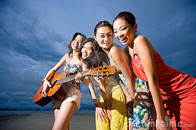 Fun group of girls playing guitar at the beach
