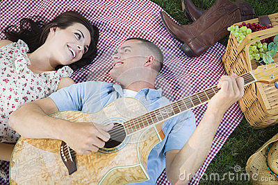 Fun Mixed Race Couple Playing Guitar and Singing