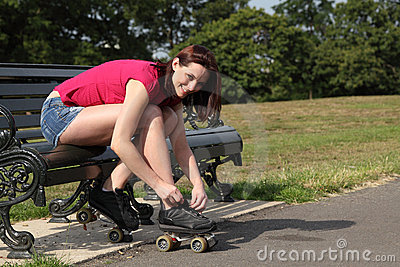 Fun time in sun beautiful girl putting on skates