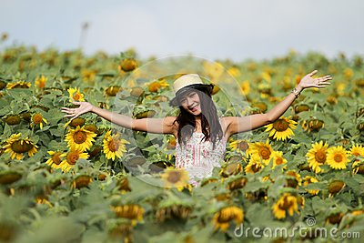 Fun woman in the field of sunflowers