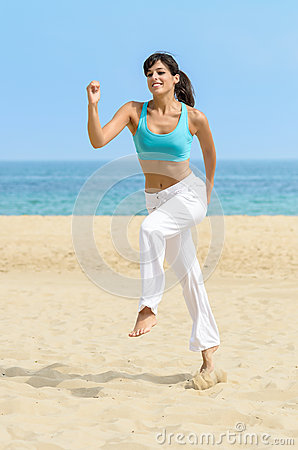 Fun woman running jumping on beach