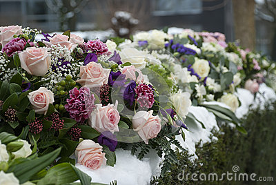 Funeral flowers arrangement in the snow on a cemetery