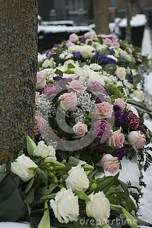 Funeral flowers arrangement in the snowon a cemetery