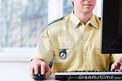 Funkcjonariusz Policji pracuje na biurku w dziale